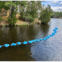 The poms on a rope can be used over open water and secured to the shoreline.